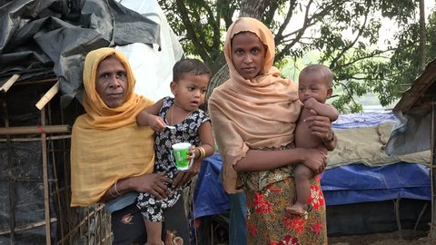 TEKNAF, BANGLADESH - OCTOBER 25, 2017: A group of Rohingya refugee women from Myanmar are standing in a group and looking helpless in the camera