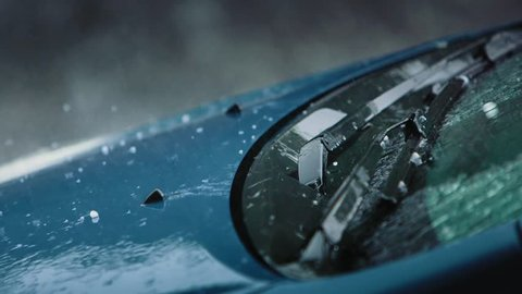 Slow motion shot of heavy rain and hailstones slamming against a car