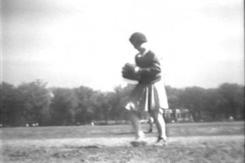 CIRCA 1930s - A girl pitches strikeouts and hits a home run in a baseball game, in Brooklyn, New York, in 1932.