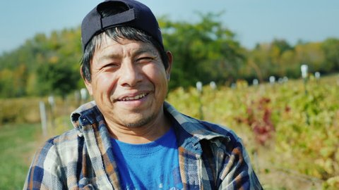 Portrait of a Mexican working farmer. Standing on the field, looking at the camera, smiling