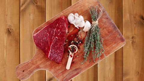 fresh raw beef meat fillet flesh with peppercorn and thyme ready to grill on wood board isolated over white background