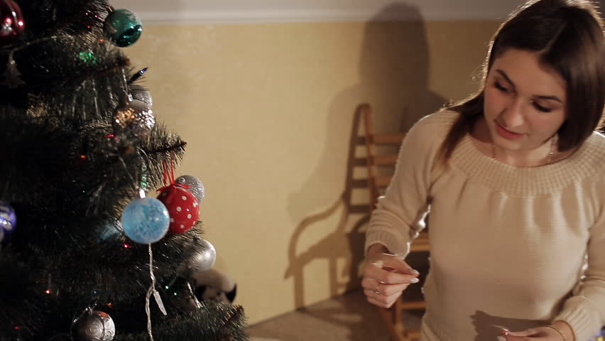 young beautiful brunette in a knitted suit decorates on a Christmas tree. light of a flickering garland and candles