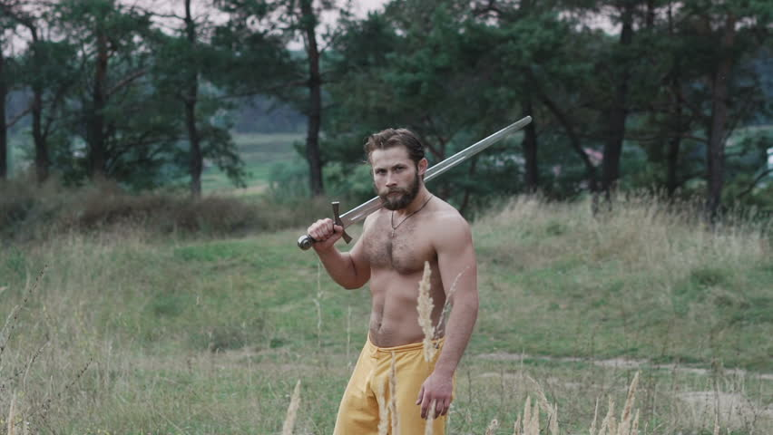 Handsome free fighter with sword walks in a steppe. Slowly #32282818