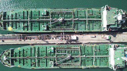Aerial shot of two tanker ships anchored at the oil terminal at port