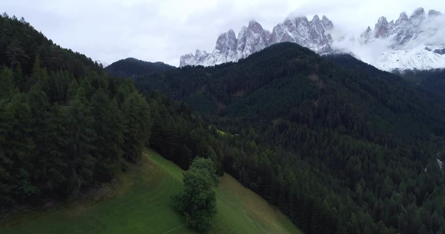 Amazing aerial shot of Dolomiti mountain on a cloudy autumn day. Flying above beautiful green forest in Santa Maddalena in Val di Funes, Dolomites, Italy with view over Italian Alps.