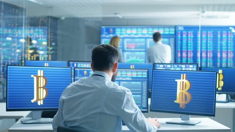 Back View of the Stock Trader Raising His Arms in Big Victory, He's Working for the Cryptocurrency Exchange Department. Screens Show Relevant Data,Graphs and Ticker Numbers,Other People in the Office.