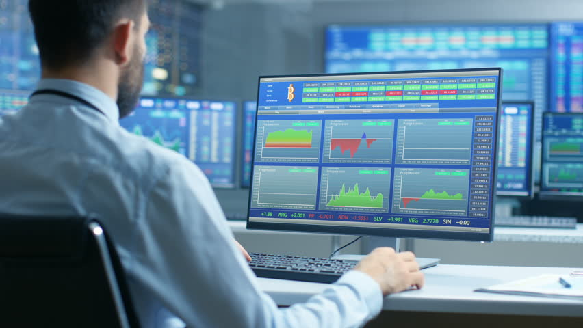 Stock Market Trader Observes Up's and Down's of the Market at His Workstation, Sells/ Buys Stocks and Bonds. Room is Full of Screen Showing Relevant Numbers. Shot on RED EPIC-W 8K Helium Cinema Camera | Shutterstock HD Video #32307538