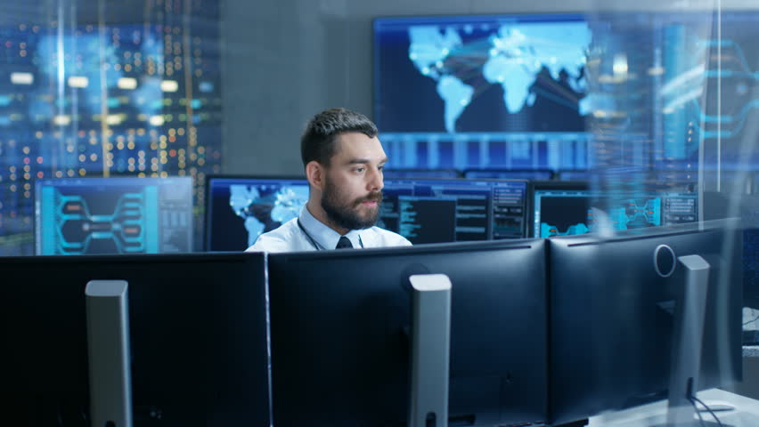 In the System Control Center Technical Operator Monitors Displays at His Workstation. He's Surrounded by Displays Showing Relevant Data. In the Background Data with Interactive Map.  | Shutterstock HD Video #32307757