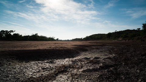 A linear daytime timelapse showing a dry riverbed with mud cracks drying up as the heat of the day increases with cumulous clouds moving across. 4K