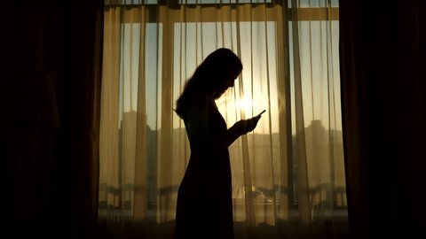 Young woman stay bend head over smart phone, silhouetted half-length profile shot against living room window. Bright sun shine outside through  transparent curtain. Girl touch screen of mobile device