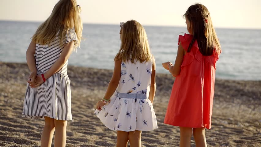 three little girl is wearing different color summer dress are running and jumping on a pebble beach
