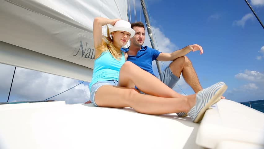 Cheerful couple cruising on a catamaran in Caribbean sea