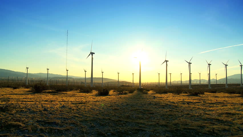 Wind turbines producing clean alternative energy in silhouette at sunset