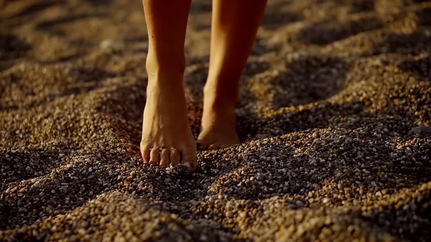 Barefoot woman is walking over a coarse sand in evening time, sun is shining at an angle | Shutterstock HD Video #32360158