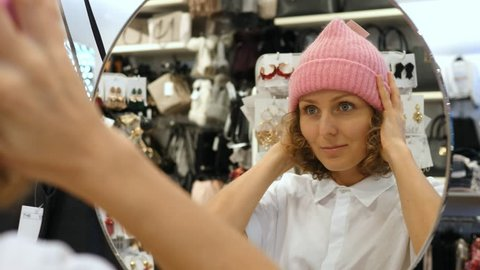 Young Woman Shopper Trying On Knit Hat Looking In Mirror In Clothing Shop. Closeup. 4K.