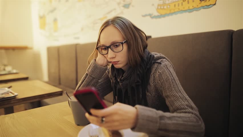 A frustrated young girl in glasses misses the cafe. The tired woman is waiting for the boyfriend and is bored with the phone in her hands. Love and relationships.