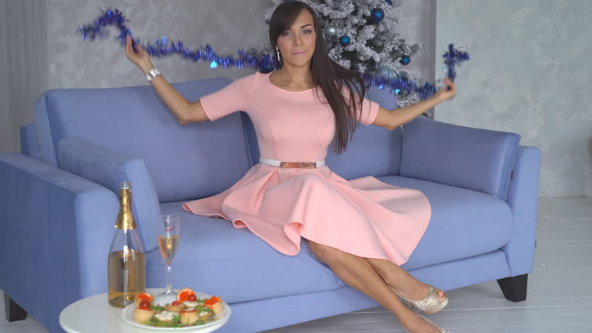 Beautiful sexy brunette sitting on the couch by the fireplace and drinking champagne. woman with a beautiful evening dress of peach color. A woman wears a blue New Year's tinsel on her neck. in his   Shutterstock HD Video #32380288