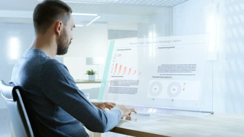In the Near Future Renewable Energy Scientist Works with Touchscreen Transparent Computer Display. Screen Shows Interactive User Interface with Flowing Pie Charts, Graphs. 4K UHD.