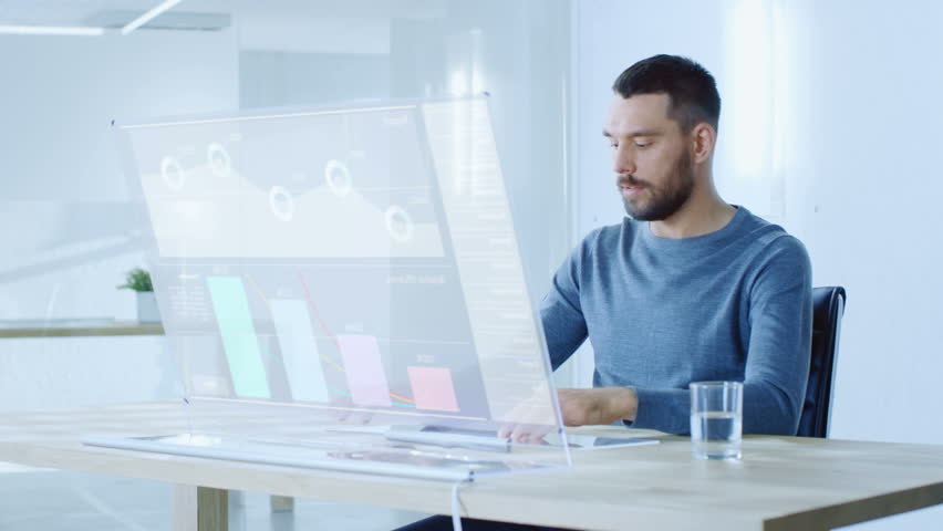 In the Near Future Man Sitting at His Workstation, Works on His Modern Computer With Transparent Display. Display Shows User Interface with Interactive Charts and Graphics. 4K UHD. | Shutterstock HD Video #32413108