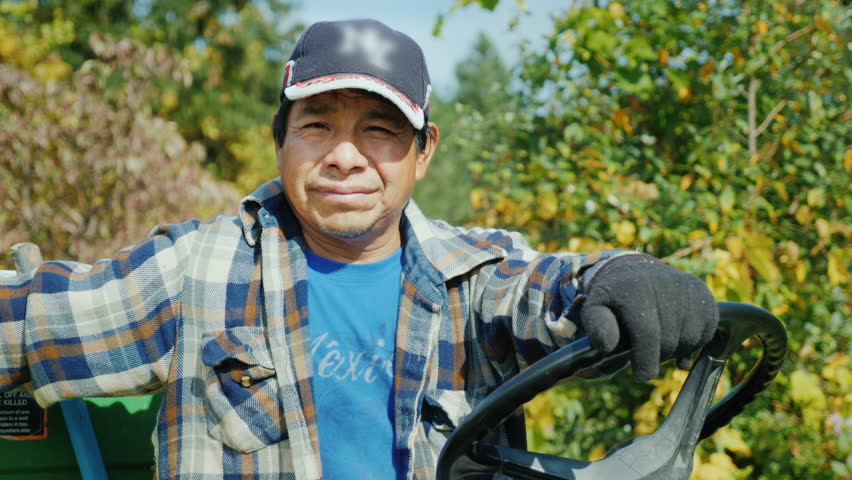 A Mexican worker is sitting behind the wheel of a small tractor.