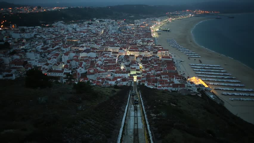 Nazare, Portugal by evening, the most popular seaside resorts in Silver Coast. Prospective view of popular Ascensor da Nazare or Nazare Funicular from Nazare Sitio, the upper part of city. slow motion