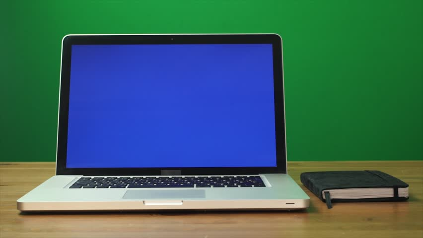 Laptop with a green screen and black notepad on table. Green screen background. Dolly shot. Zoom out motion   Shutterstock HD Video #32450818