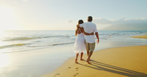 Happy couple walking down the beach at sunset