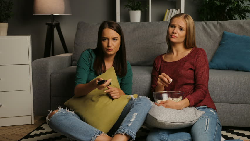 Female friends with popcorn sitting on the floor and watching melodrama movie in the cosy living room. Indoor | Shutterstock HD Video #32480338