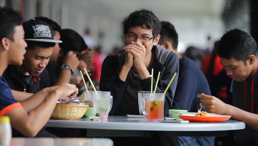 IPOH, MALAYSIA - NOVEMBER 04, 2017. Group of Malay teenager talking each other as they enjoy their meal at the food court in Ipoh, Perak.