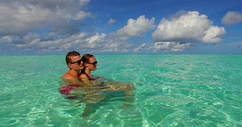 v15508 two 2 people together having fun man and woman together a romantic young couple sunbathing on a tropical island of white sand beach and blue sky and sea