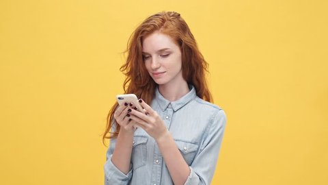 Happy ginger woman in denim shirt holding and using smartphone over yellow background