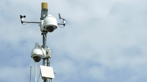 Security Cameras. Pole with video surveillance system, vane and anemometer, with blue sky and clouds background.