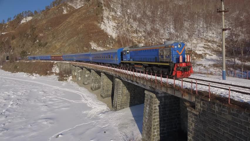 Close approach passengers train Trans Siberian railway brick bridge. Frozen lake Baikal coast. Winter beautiful Holiday  Russia. Sunny day snow field high rocks. Fast speed aerial drone 4k footage.