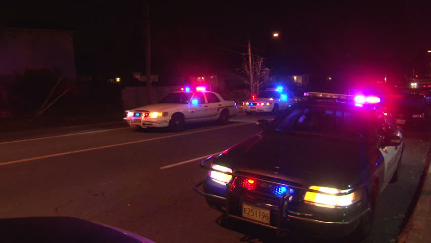 PORTLAND, OREGON - CIRCA DECEMBER 2012: Police lights flashing at night downtown at crime scene, zoom out.