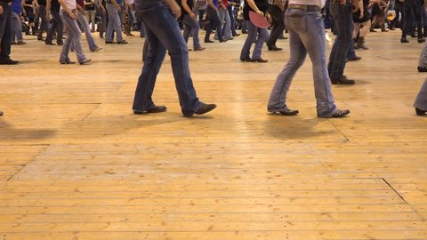 Legs moving together at American horse festival. Music tradition jeans boots and flag. People dancing cowboy line dance at a folk country event, USA style
