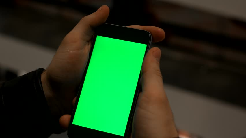 Closeup of male hands holding smart phone with green screen prekeyed for effects
