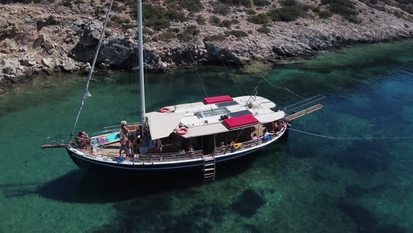 Birds eye view of boat anchored in Paros, Greece. Flying above turquoise waters on Greek island holiday. Aerial 4k footage for Paros tourism and sightseeing.