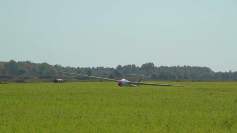 The small sailplane on the grassy field about to take off the air