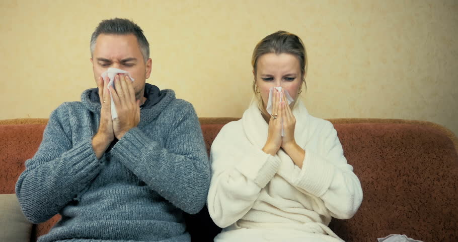 Young guy and girl sneeze and wipe snot with a handkerchief sitting at home on the sofa.