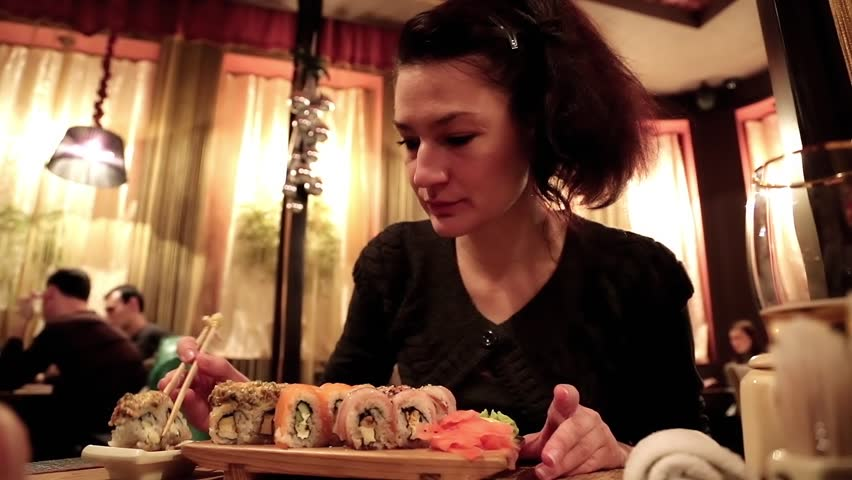 Woman eating sushi in a Japanese restaurant