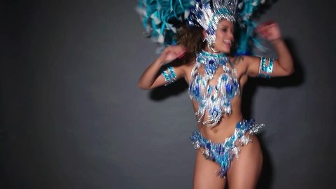 Beautiful and happy woman dancing samba while wearing traditional blue costume