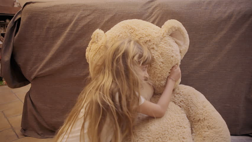 A cute little girl jumping on her toy, a giant teddybear, and hugging him. Funny lifestyle shot. Jump from the left.