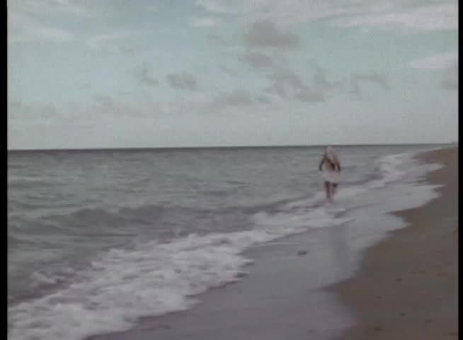 Rear view of person running on beach
