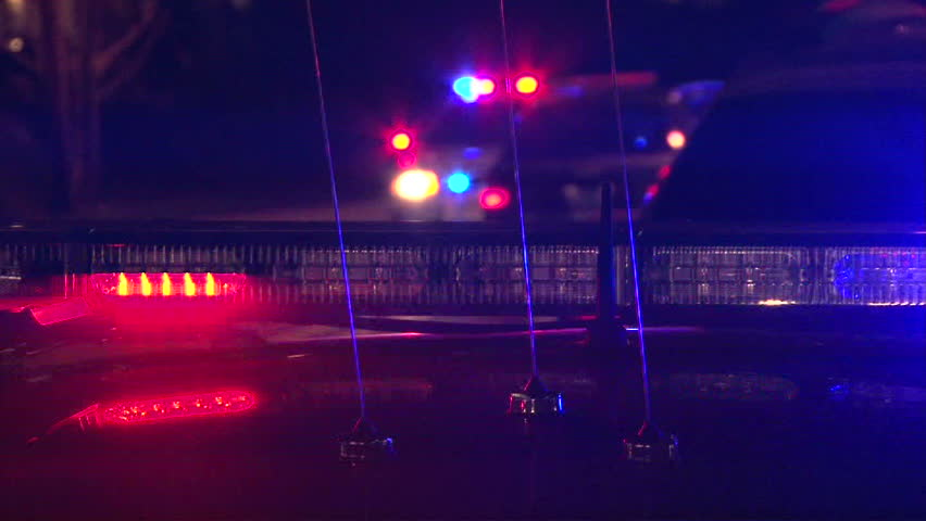 Police lights flashing at night downtown at crime scene.