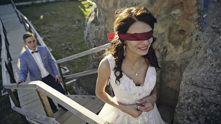Newly married couple walking along wooden path among rocks, blindfolded bride going upstairs.