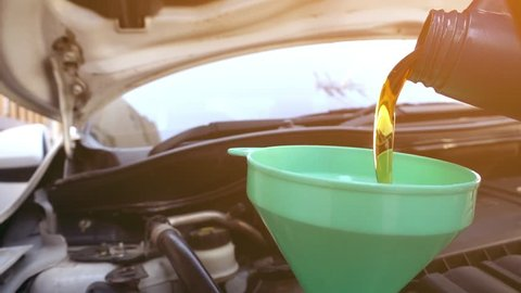 Super slow motion Pouring fresh new clean synthetic oil into car's engine, closeup.