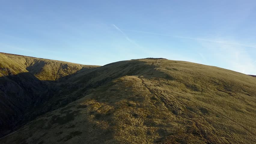 Aerial footage of walkers in the cheviot hills, with walkers silhouetted along the ridge, and beautiful golden sunlight