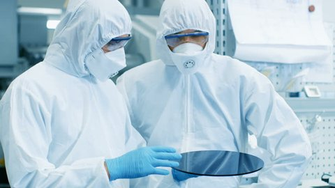 Two Engineers/ Scientists/ Technicians in Sterile Suits Check Semiconductor Silicon Wafer. They Work in a Modern Semiconductor Fabrication Plant. Shot on RED EPIC-W 8K Helium Cinema Camera.