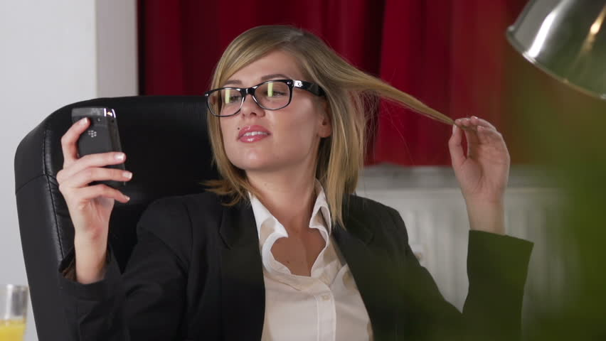 Attractive Businesswoman Reads Text Messages On Her Phone And Plays With Her Hair | Shutterstock HD Video #3275588