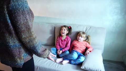 Two young sisters from European family sit on light sofa and listen to mom's remarks about bad behavior. Interior made in restrained Scandinavian style, children dissatisfied with frustrated